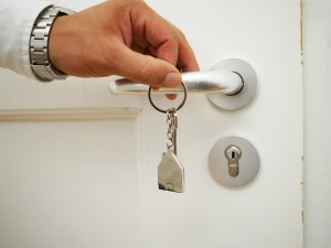 Hand holding a door knob and a set of keys.