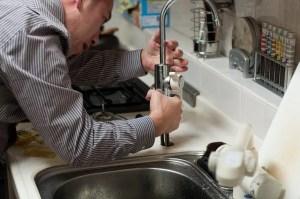 A repairman fixing a sink.