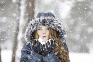 A redhead girl standing in the snow.
