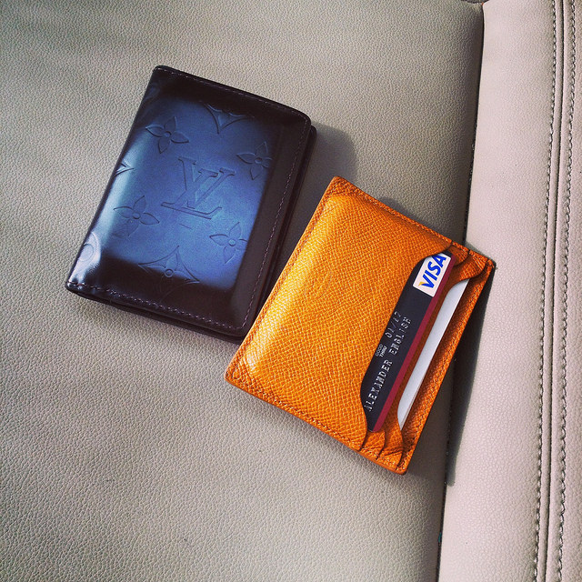 Two cherished once-used wallets: Louis Vuitton monogram glace and Tod's bright mandarin orange card case