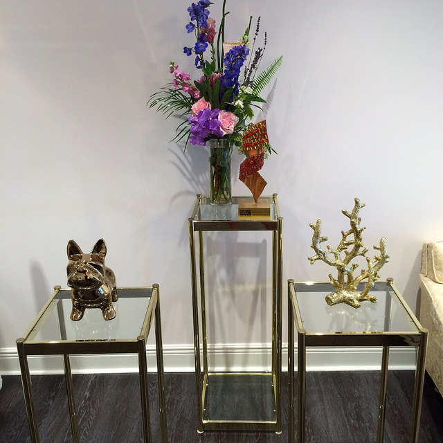 Sitting area decor is all modern, gold, glass, chrome, and pale pink or white