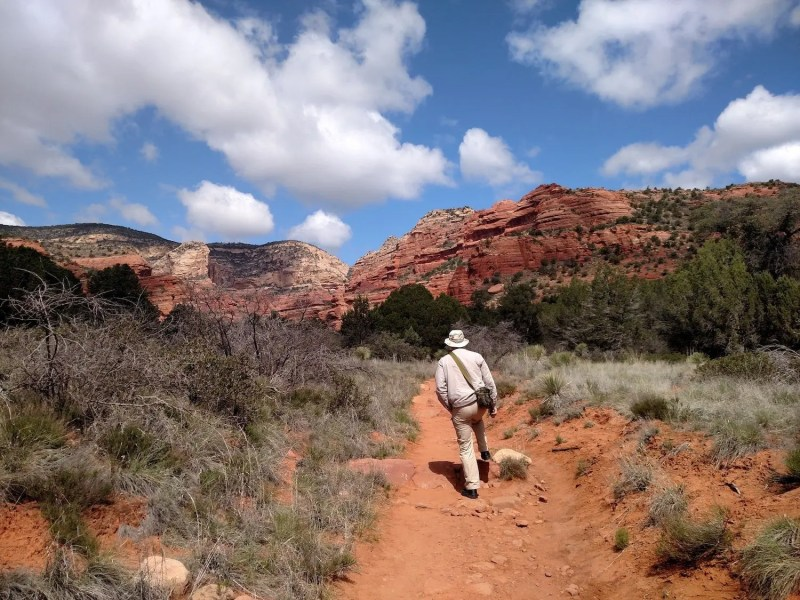man hiking outside in red rock with cannabis