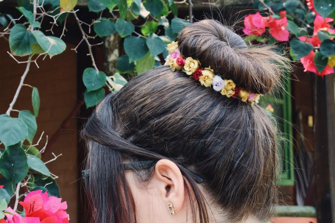 Foto usando uma tiara de flores em um coque da Flower Store