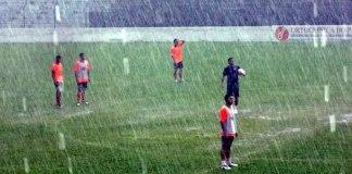 Jogadores treinam em baixo de chuva