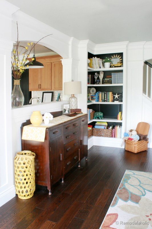 Living Room Remodel with yellow accents wood floors and built-in bookcases and columns with arches-21