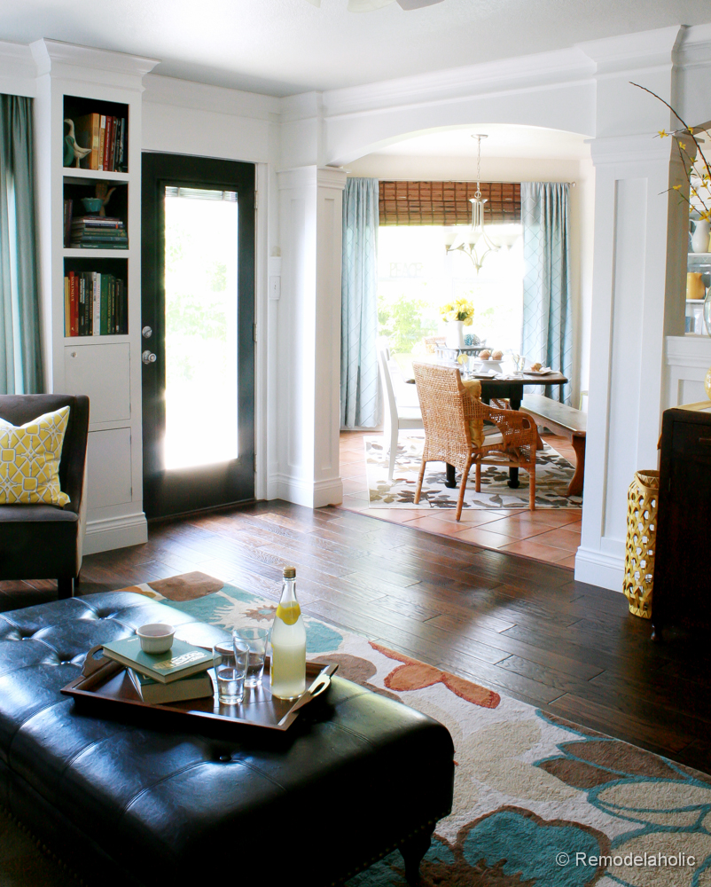 Living Room Remodel With Yellow Accents Wood Floors And Built In Bookcases  And Columns With
