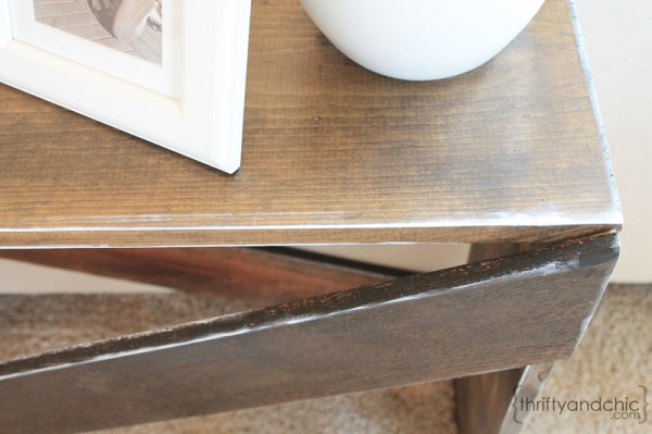 detail of white distressing on X-base sofa table, featured on Remodelaholic.com