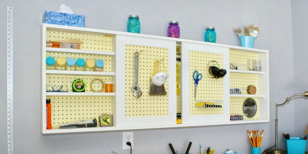pegboard tool cabinet with sliding doors, featured on Remodelaholic.com