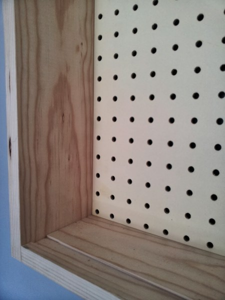 groove in pine board to allow tool cabinet doors to slide smoothly, featured on Remodelaholic.com