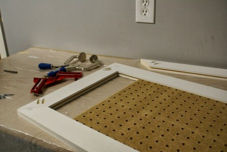 installing pegboard in doors of tool cabinet, featured on Remodelaholic.com