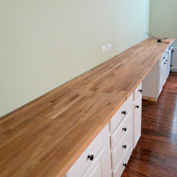 IKEA butcherblock countertop for built-in wall-to-wall desk, Home Is Where My Heart Is featured on Remodelaholic
