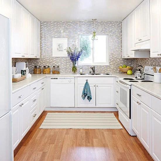 U shaped kitchen with white cabinets and full tile backsplash wall via BHG