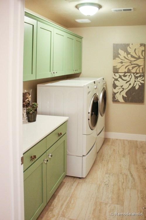 Jolies armoires vertes dans une buanderie à un mur. Fabuleuses idées de conception de salle de lavage de @Remodelaholic