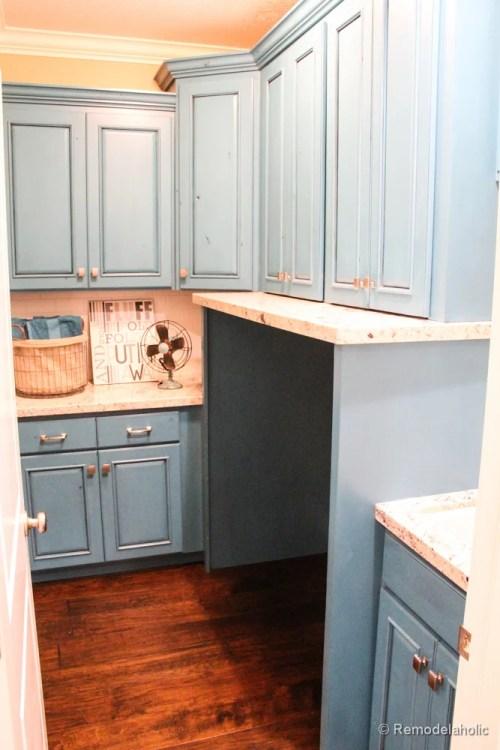 Fabuleuses idées de conception de buanderie d'armoires bleues @RemodelaholicPretty avec une zone intégrée pour les machines.