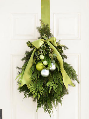 evergreen and ornament door swag - Good Housekeeping via @Remodelaholic