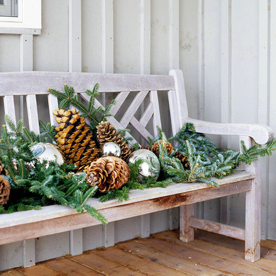 fresh evergreen branches on an entry porch bench - BHG via @Remodelaholic