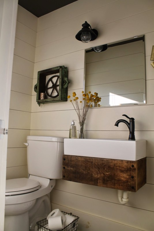 rustic reclaimed wood floating vanity in bathroom with planked walls - Girl Meets Carpenter featured on @Remodelaholic