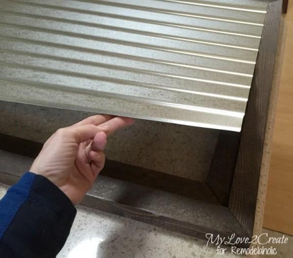 placing corrugated metal inside wood frame