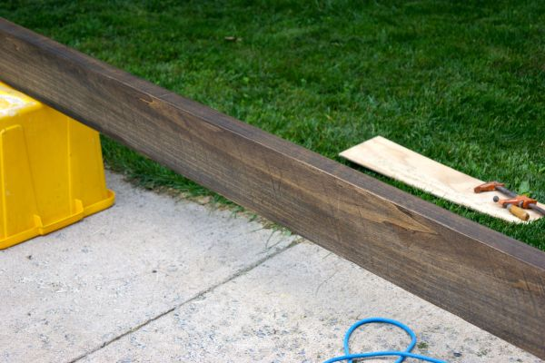 stained rough cut lumber for wooden floating shelf in bathroom