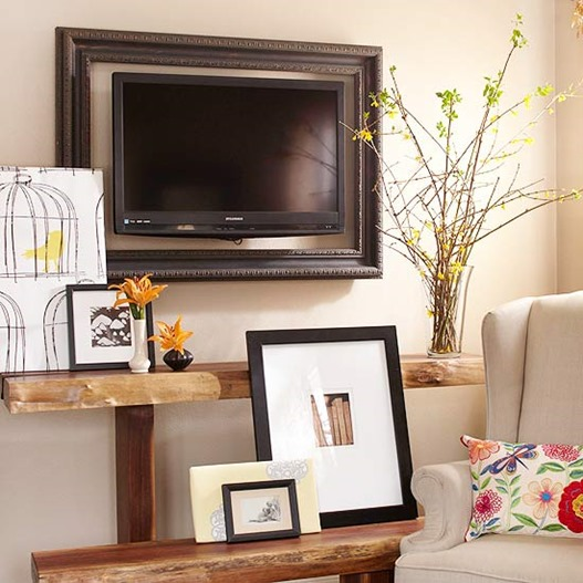 layered decor and shelving around a framed television to help it blend in (BHG)