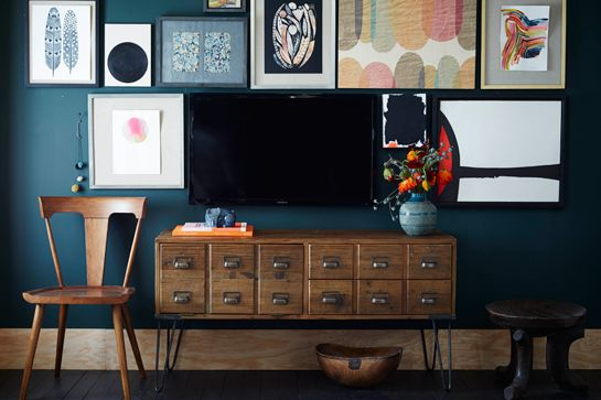 paint a dark wall behind the TV and hang a gallery wall to hide the television (West Elm via Refinery 29)
