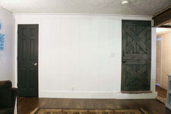 interior door in Iron Ore, with a real wood dutch barn door colorwashed and stained to match, along a tall white board and batten wall (Remodelaholic)