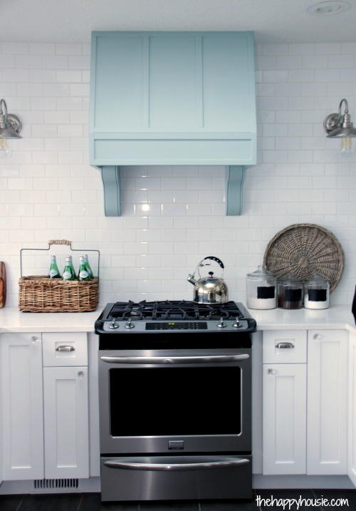 The Happy Housie white kitchen and blue range hood with corbels