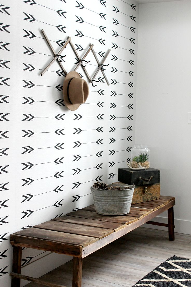 Monochrome Entry Inspiration: Love the simplicity here. Modern graphic black and white arrow wallpaper, with a rustic simple bench, and a black lattice style rug. Perfection!