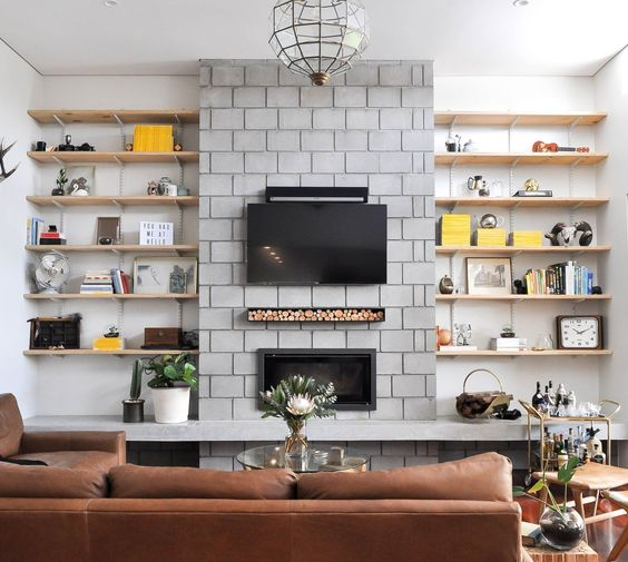 Love the rustic rough industrial look to this concrete fireplace with track shelving to the sides!