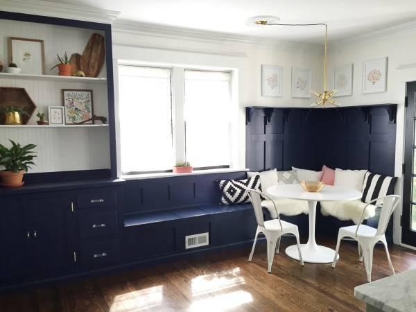 Gorgeous navy dining room banquette plus built-in hutch. The paneled board and batten below the ledge is gorgeous above the banquette!
