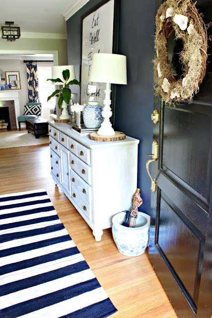 The navy wall in this foyer is gorgeous! And the wood slice under the lamps is a fun rustic touch to a more traditional space. | 100+ Beautiful Mudrooms and Entryways at Remodelaholic.com
