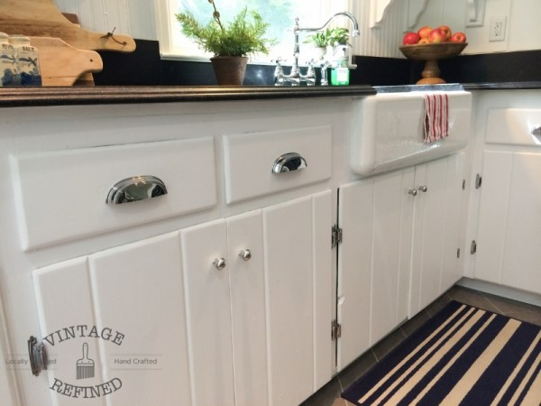 Chrome drawer pulls maintain classic feel in lakehouse kitchen remodel, black and white kitchen, by Vintage Refined featured on @Remodelaholic