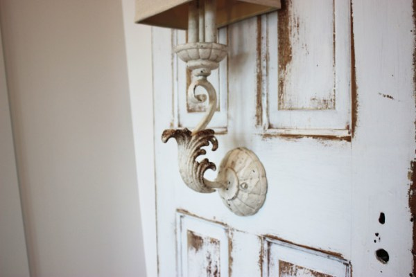 Wall sconce mounted on antique door used as bedside lighting, by Simple Nature Decor featured on @Remodelaholic