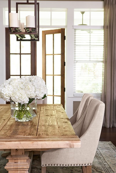 farmhouse dining room with swoop arm chairs and rustic wood table by Linda McDonald Design