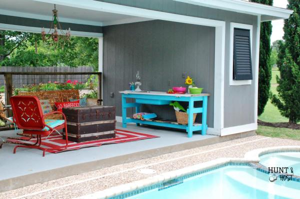 DIY upcycled door into poolside table by Hunt and Host featured on @Remodelaholic