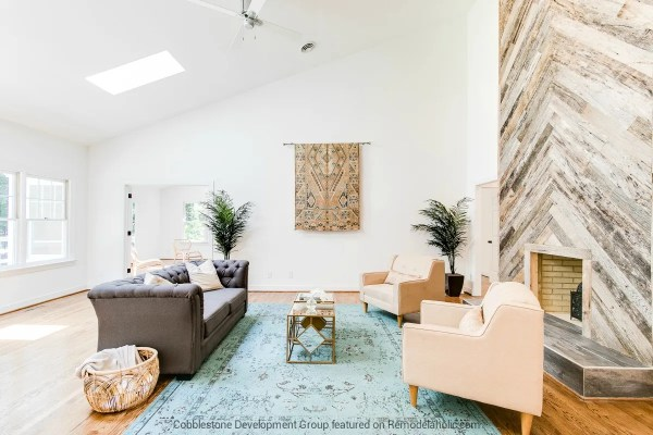 Beautiful 1980's Open Living Room Renovation with Herringbone Wood Fireplace, Fendall Home Renovation, Cobblestone Development Group featured on @Remodelaholic
