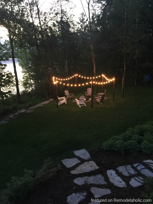 DIY outdoor lighting posts for string lights around a fire pit, featured on @Remodelaholic wm