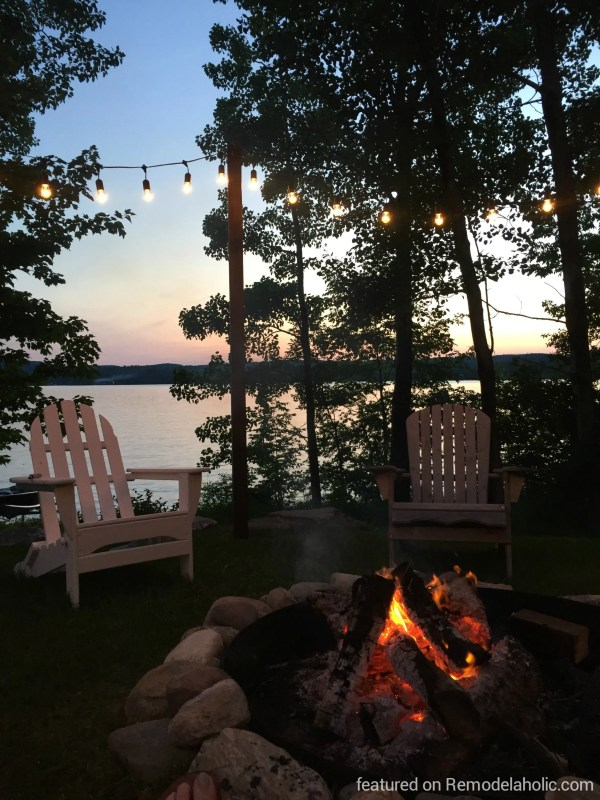 Easy DIY outdoor lighting posts around a fire pit with seating area, featured on @Remodelaholic wm