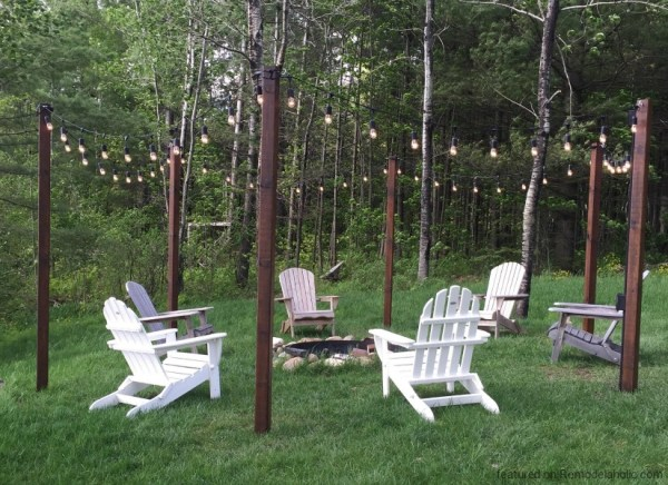 feat DIY easy outdoor string lighting posts around a fire pit and seating area, featured on @Remodelaholic