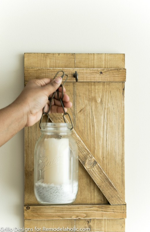 Bring the rustic farmhouse style home with this easy and inexpensive mason jar candle holder or vase. It's easy to make your own hanging mason jar!