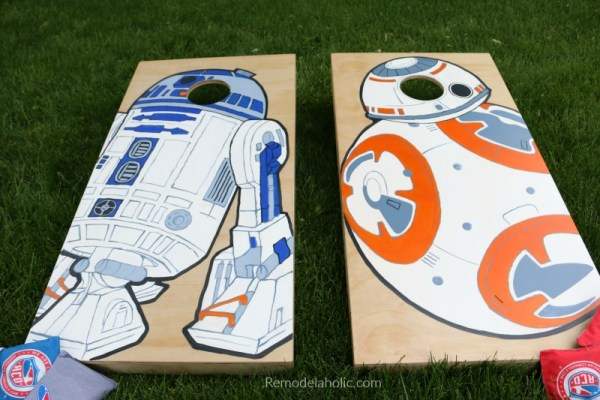 Large DIY Wall Decor for Patio: custom painted cornhole boards painted with Star Wars droids BB-8 and R2-D2, on the grass in a backyard