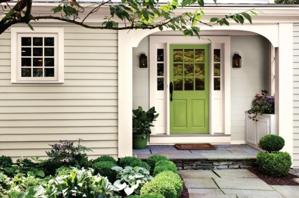 Tan House With Bright Green Front Door And Green Plants In Flower Garden
