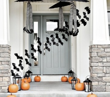 Gorgeous Front Door With Pumpkins, Black Lanters, Plastic Bats Taped Across The Porch And Witches Legs In Striped Tights And Black Heels Under Black Umbrellas