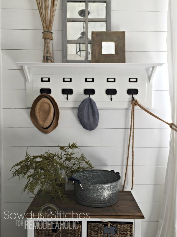 White Shiplap Walls With White Wooden Shelf And Black Hooks, Window Mirror Above, Wooden And White Bench Below With Wisker Baskets