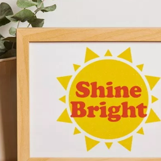 Wooden Frame With Yellow Sun Image And Shine Bright Wording Across The Sun