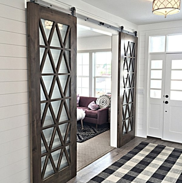 Entryway With Sliding Barn Doors To Living Room, Black And White Checkered Rug In Entry And Purple Couches Seen Through Doorway