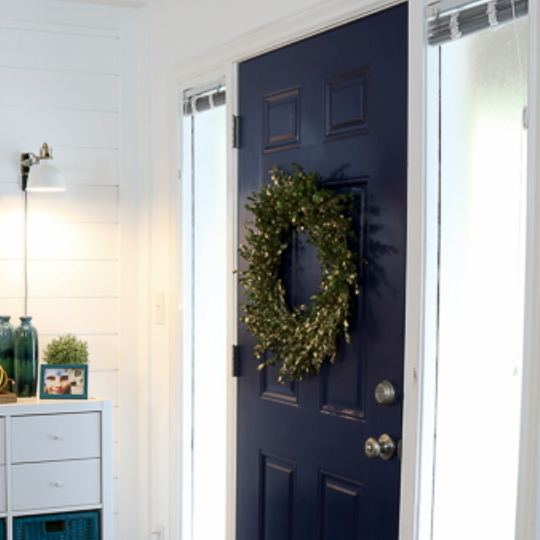 White Walls With Beautiful Blue Door And Green Wreath