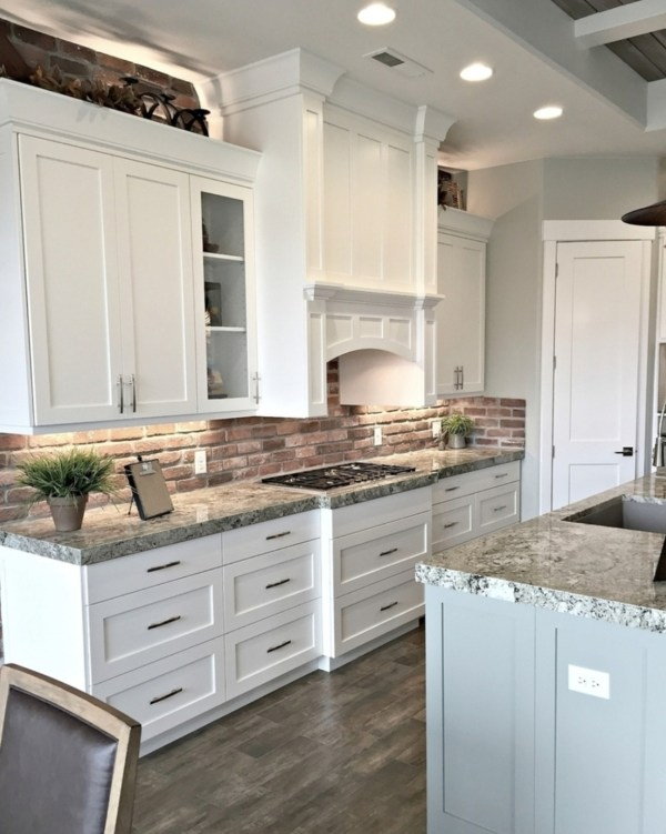 Kitchen With White Cabinets, Granite Countertops, Blue Island, And Brick Backsplash