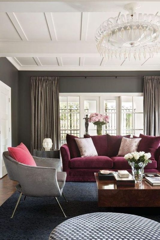 Living Room With Grey Walls, White Accented Ceiling, Chandalier, Burgundy Couch, Grey Chair And Wood Table