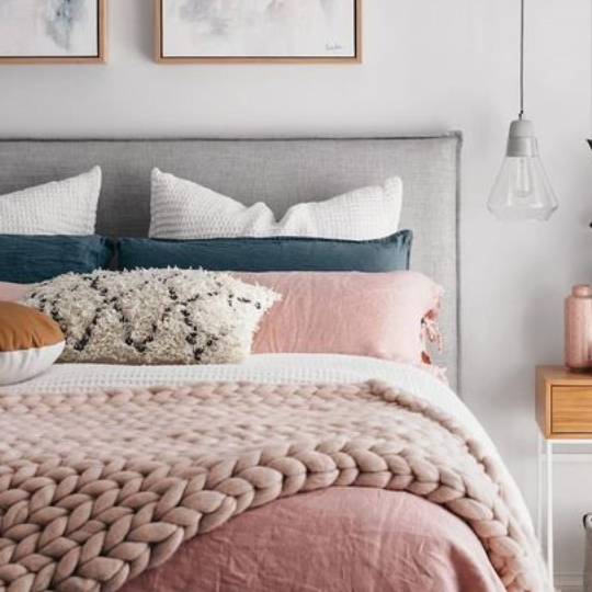 Bedroom With White Walls, Grey Headboard, Pink Comforter And Pillows With Blue And White Accents